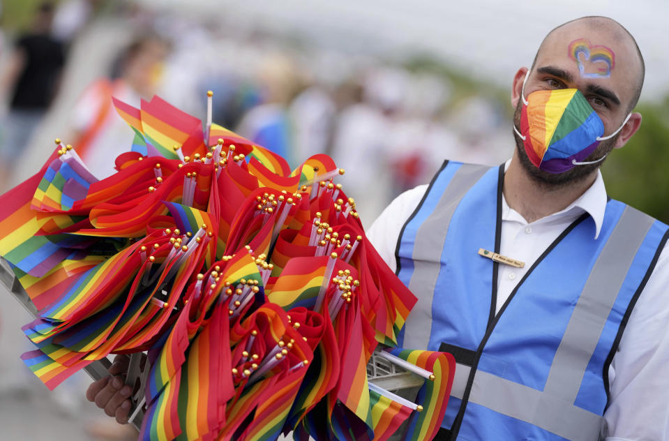 A man offers LGBT pride flags to football supporters outside of the stadium before the Euro 2020 soccer championship group F match between Germany and Hungary at the Allianz Arena in Munich, Germany,Wednesday, June 23, 2021. (AP Photo/Matthias Schrader)