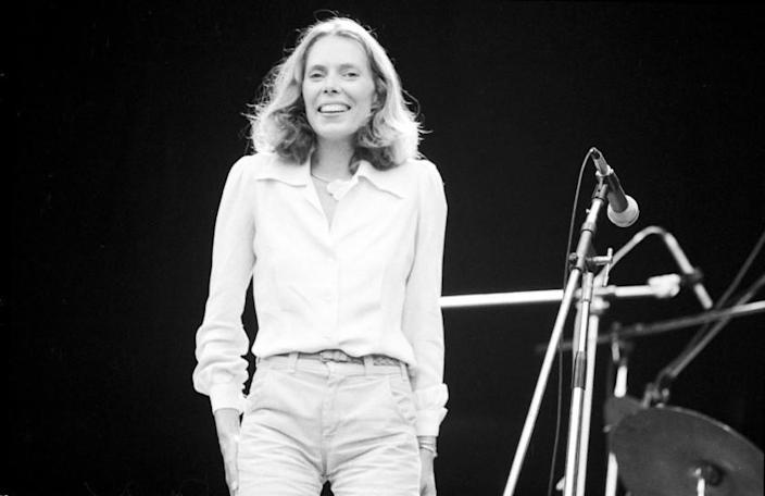 A black and white image of a woman standing onstage in front of a microphone
