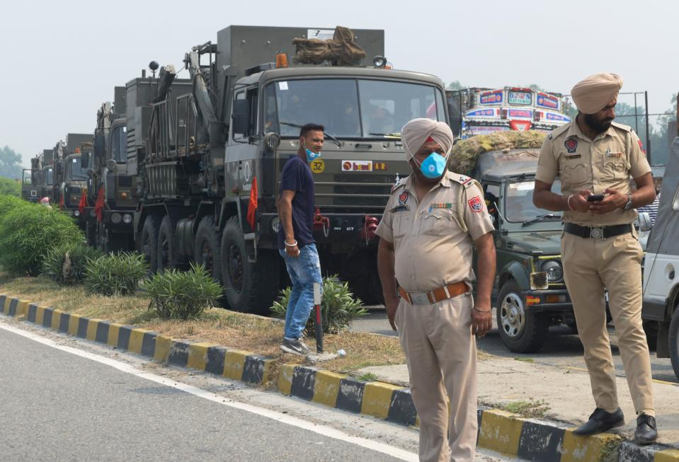 Punjab Police personnel stand guard near the Army convoy along a national highway blocked by farmers during a nationwide farmers' strike following the recent passing of agriculture bills in the Lok Sabha (lower house), on the outskirts of Amritsar on September 25, 2020. (Photo by NARINDER NANU/AFP via Getty Images)