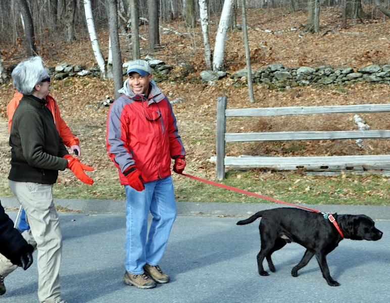 This Jan. 1, 2012 publicity image provided by Massachusetts State Department of Conservation and Recreation shows Gov. Patrick Deval and his dog Tobey, participating in a First Day hike at Mount Greylock State Reservation in Lanesborough, Mass. Massachusetts has organized hikes in state parks on New Year's Day for more than 20 years. An effort by a group called America's State Parks to expand the program last January succeeded in getting 14,000 people to take part in hikes in 400 parks in 50 states. This coming Jan. 1, the program is expected to be even bigger. (AP Photo/Tim Zelazo/ MassParks Department of Conservation and Recreation Staff)