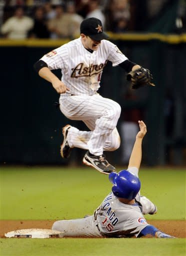 Houston Astros shortstop Jed Lowrie (4) jumps to avoid a sliding Chicago Cubs' Darwin Barney (15) inning of a baseball game Wednesday, Sept. 12, 2012, in Houston. Barney was out but broke up the possible double play attempt. (AP Photo/Pat Sullivan)