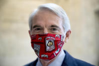 FILE - In this file photo from May 20, 2020, Sen. Rob Portman, R-Ohio, wears an Ohio State University mask as the Senate Homeland Security and Governmental Affairs committee meets on Capitol Hill in Washington. Sometimes at odds, America's two largest generations have something to agree on: the coronavirus pandemic has smacked many at a pivotal time in their lives. For baby boomers, named for the post-World War II surge of births, that means those who retired or are nearing retirement age are seeing their retirement accounts appearing unreliable while their health is at high risk. Millennials, who became young adults in this century, are getting socked again as they were still recovering from the Great Recession. (AP Photo/Andrew Harnik)