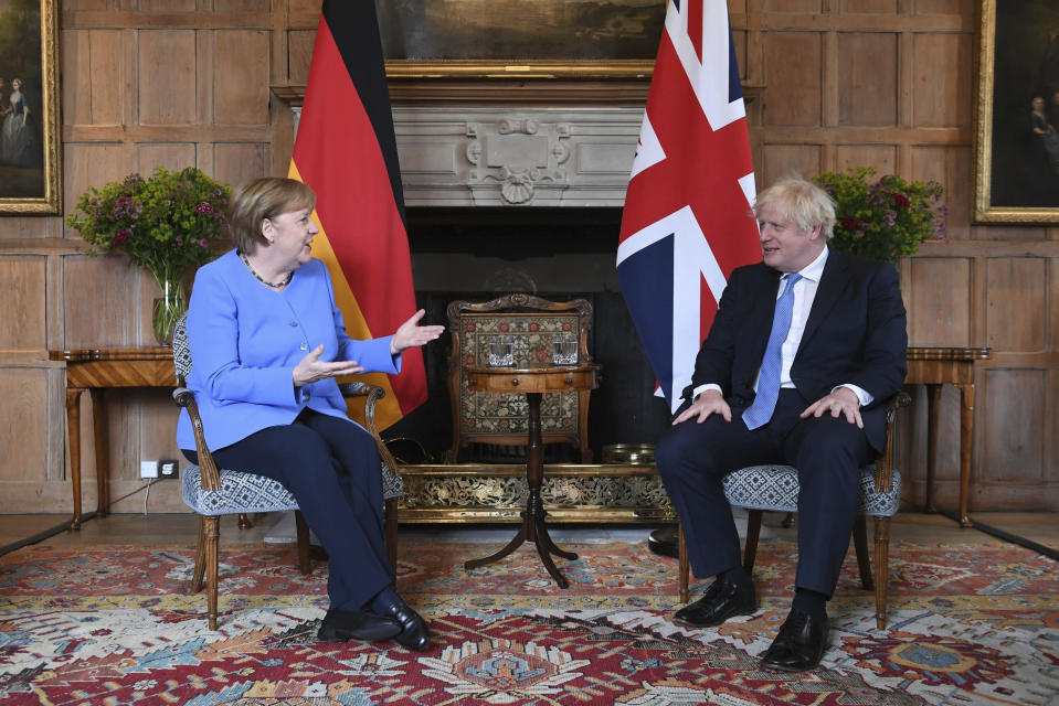 Britain's Prime Minister Boris Johnson, right, reacts with German Chancellor Angela Merkel, before their bilateral meeting at Chequers, the country house of the Prime Minister, in Buckinghamshire, England, Friday July 2, 2021. Johnson is likely to push Angela Merkel to drop her efforts to impose COVID-19 restrictions on British travelers as the German chancellor makes her final visit to Britain before stepping down in the coming months. Johnson will hold talks with Merkel at his country residence on Friday. (Stefan Rousseau/Pool Photo via AP)
