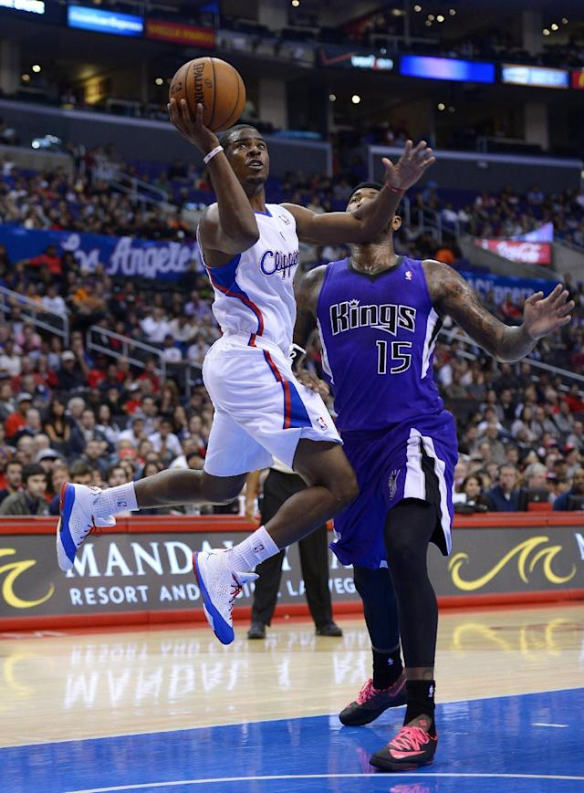 Los Angeles Clippers point guard Chris Paul, left, puts up a shot as Sacramento Kings center DeMarcus Cousins defends during the first half of their NBA basketball game, Friday, Oct. 25, 2013, in Los Angeles. (AP Photo/Mark J. Terrill)