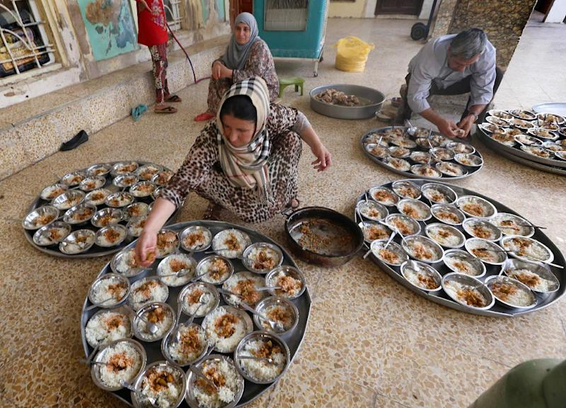 An Iraqi Kurdish woman puts the final touches to bowls of food on the first day of the holy Muslim month of Ramadan, for families who fled the violence in the northern province of Nineveh, at a mosque in Arbil, on June 29, 2014 (AFP Photo/Safin Hamed )