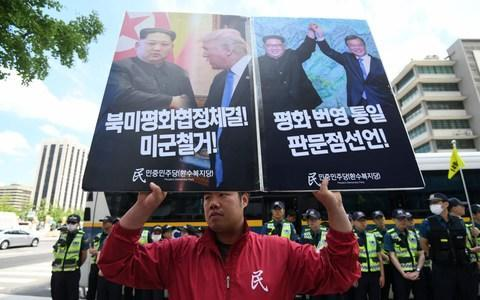 Protests, however, were held in South Korea where president Moon Jae-in watched on hopefully - Credit: JUNG YEON-JE/AFP