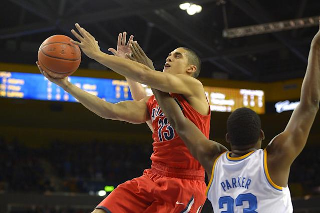 Arizona guard Nick Johnson, left, shoots as UCLA center Tony Parker defends during the first half of an NCAA college basketball game on Thursday, Jan. 9, 2014, in Los Angeles. (AP Photo/Mark J. Terrill)