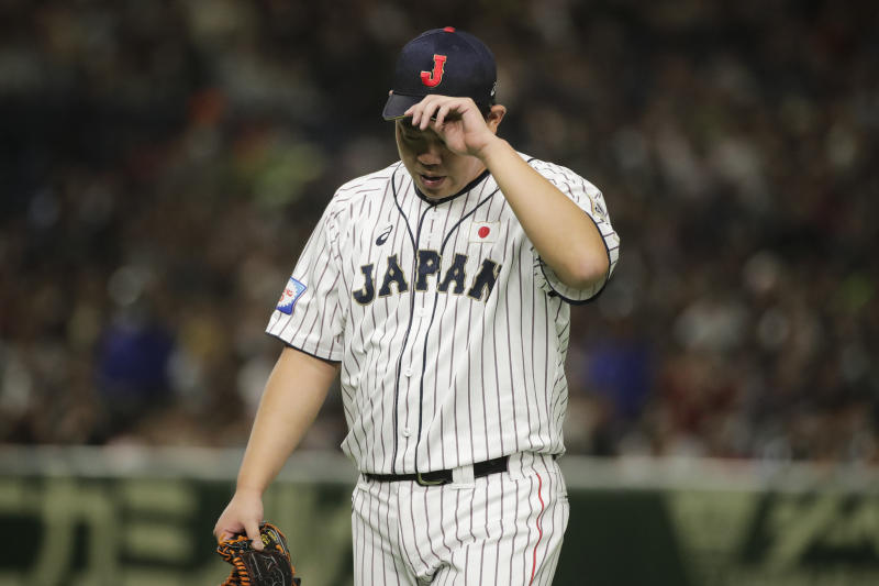 Japan starting pitcher Shun Yamaguchi walks off the field after the top of the first inning of the Premier12 baseball tournament final game against South Korea at Tokyo Dome in Tokyo Sunday, Nov. 17, 2019. (AP Photo/Jae C. Hong)