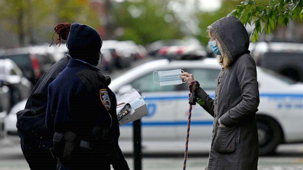 PHOTO: NYPD officers hand out free face masks on May 11, 2020 in the Brooklyn borough of New York City. (Angela Weiss/AFP via Getty Images)