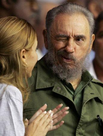 Cuban President Fidel Castro (R) winks at a woman at the graduation of hundreds of Cuban art students at Havana's Sports City in this October 28, 2005 file photo. REUTERS/Claudia Daut/File Photo