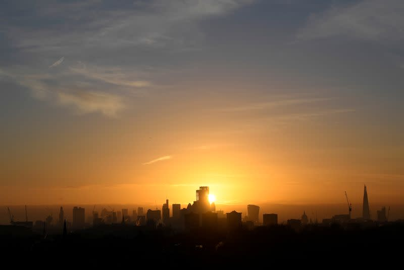 FILE PHOTO: The sun is seen rising behind skyscrapers and buildings in in the City of London financial district, London