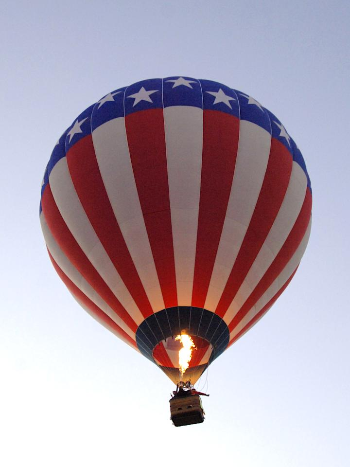 A patriotic red, white and blue balloon flies overhead  during a morning ascent at the Albuquerque International Balloon Fiesta in Albuquerque, New Mexico on October 8, 2005. (Photo by A. Messerschmidt/Getty Images)
