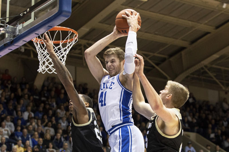 Duke's Jack White (41) grabs a rebound between Wofford's Messiah Jones, left, and Trevor Stumpe, right, during the first half of an NCAA college basketball game in Durham, N.C., Thursday, Dec. 19, 2019. (AP Photo/Ben McKeown)
