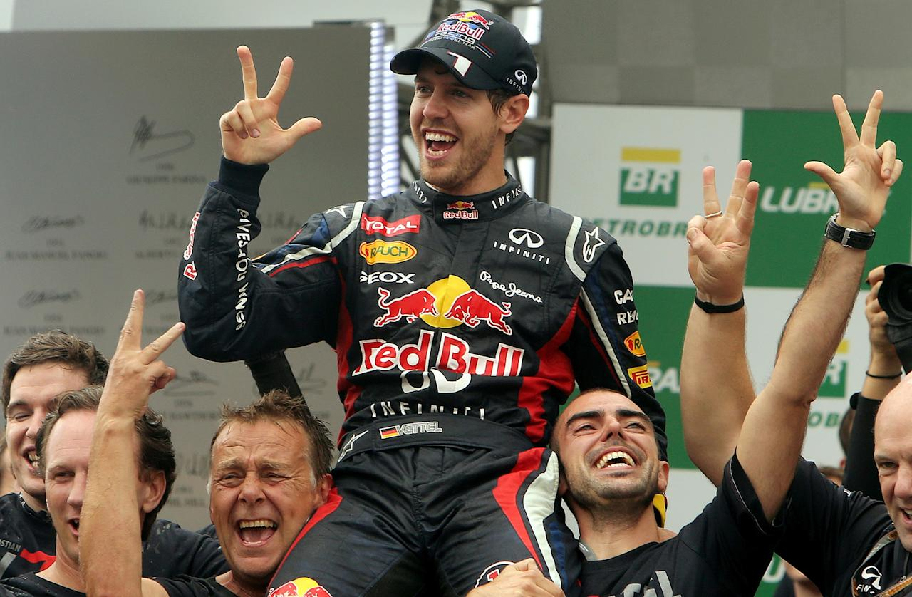 German Formula One driver Sebastian Vettel (C) celebrates his F-1 World Championship with Red Bull teammates after arriving 6th in the Brazil F-1 GP on November 25, 2012 at the Interlagos racetrack in Sao Paulo, Brazil.    TOPSHOTS/AFP PHOTO/ORLANDO KISSNERORLANDO KISSNER/AFP/Getty Images