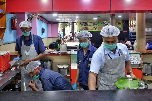 Staff members of the Indian Railway Catering and Tourism Corporation wear facemasks, as a preventive measure againsts the spread of the COVID-19 at Bangalore City Railway Station