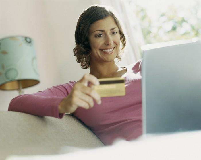A smiling woman holding a credit card, with a laptop open on her lap