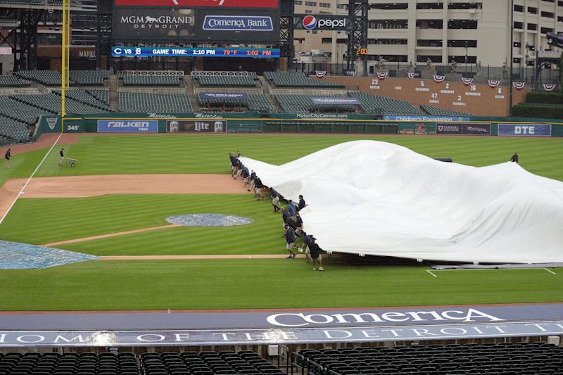 The Tigers' ground crew covers the field as rain falls before action against the Cincinnati Reds at Comerica Park, Saturday, August 1, 2020.