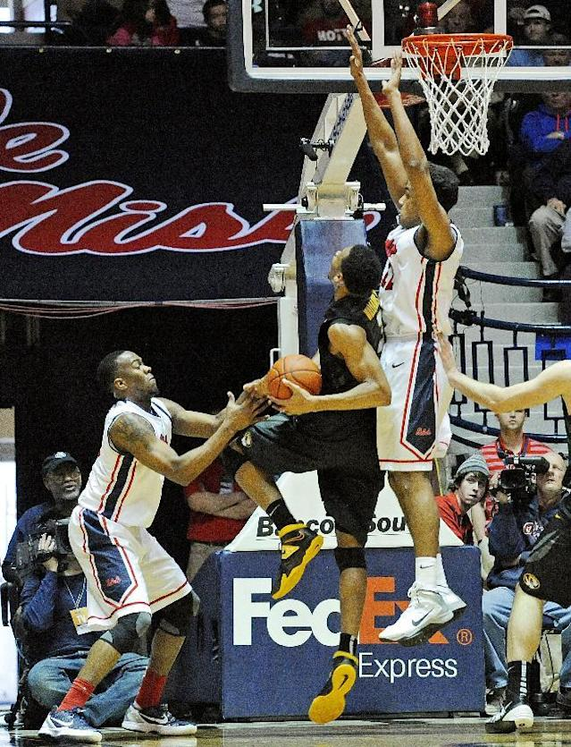 Mississippi guard Ladarius White, left, and forward Sebastian Saiz, right, block a shot by Missouri forward Johnathan Williams III (3) during the first half of an NCAA college basketball game in Oxford, Miss., Saturday, Feb. 8, 2014. (AP Photo/Thomas Graning)