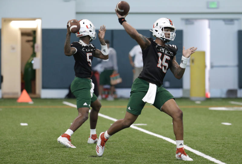 Miami quarterbacks N'Kosi Perry (5) and Jarren Williams (15) do drills during NCAA college football spring practice, Thursday, April 18, 2019, in Coral Gables, Fla. (AP Photo/Lynne Sladky)