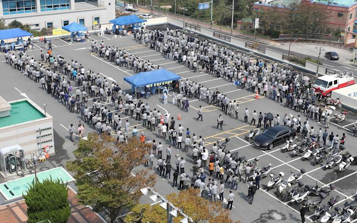 Hyundai Heavy Industries employees wait in lines to take tests for the COVID-19 coronavirus at a virus testing station in the southeastern port city of Ulsan on September 9, 2020, after seven people including company employees and their family members were confirmed as new coronavirus cases. - South Korea largely overcame an early coronavirus outbreak with extensive tracing and testing, but is now battling several outbreaks mostly linked to Protestant churches. - Yonhap/AFP
