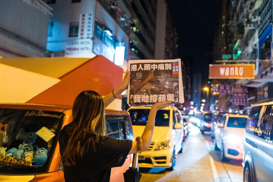 A woman holds up the final copy in the street in the early hours of Thursday morning in Hong Kong.