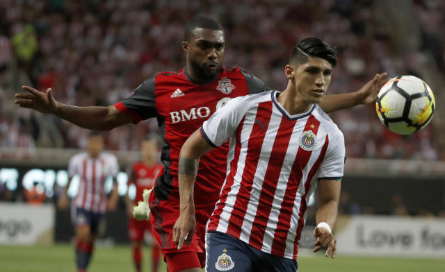 Chivas' Alan Pulido, right, fights for the ball with Toronto FC's Ashton Morgan during the CONCACAF Champions League final soccer match in Guadalajara, Mexico, Wednesday, April, 25, 2018. (AP Photo/Eduardo Verdugo)