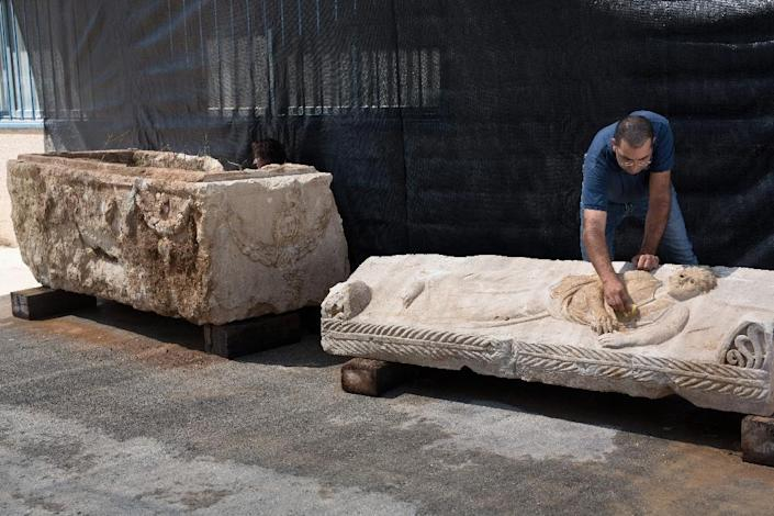 Israel Antiquities Authority southern district director Saar Ganor cleans the lid of a Roman-era sarcophagus, estimated to be 1,800 years old with carvings of Greco-Roman mythological figures, at a warehouse in Bet Shemesh, September 3, 2015 (AFP Photo/Menahem Kahana)