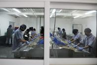 Workers process shrimp on production lines at a processing factory in Maracaibo
