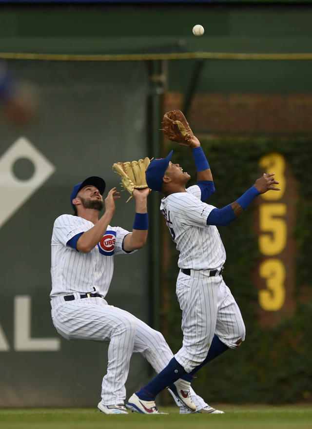 Chicago Cubs second baseman Addison Russell, right, catches a fly ball hit by Cincinnati Reds' Yasiel Puig while colliding with teammate Kris Bryant, left, during the first inning of a baseball game Monday, July 15, 2019, in Chicago. (AP Photo/Paul Beaty)