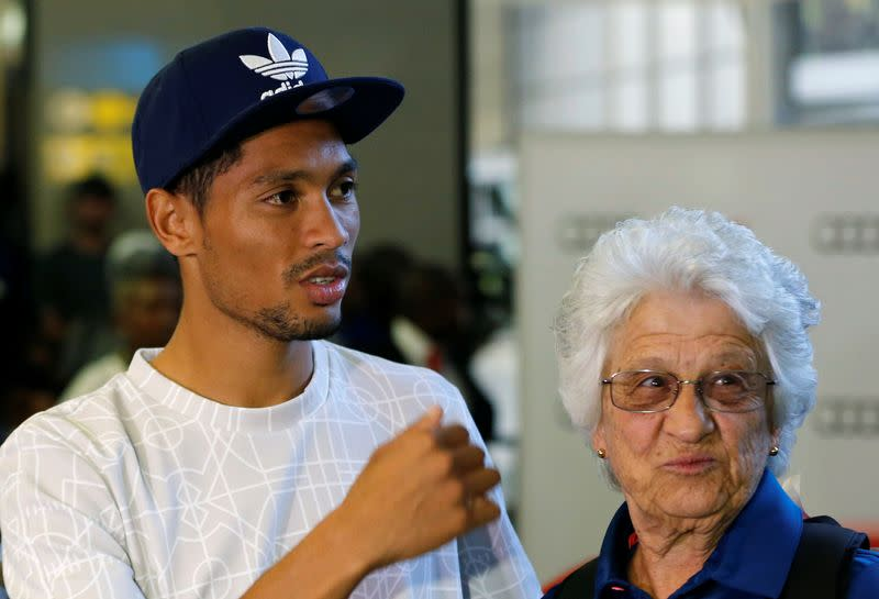 South Africa's Rio 2016 Summer Olympic Games gold medalist, Wayde van Niekerk and his coach, Ans Botha look on after their arrival at the O.R Tambo International Airport in Johannesburg
