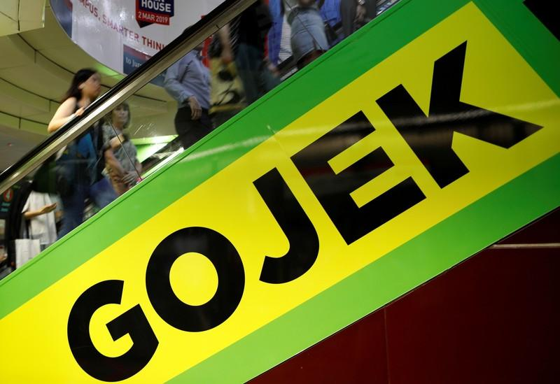 FILE PHOTO: Commuters pass by a Gojek advertisement in Singapore