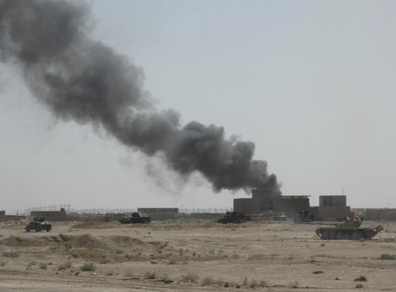 Convoy of Iraqi security forces is seen during a patrol, as smoke rises from clashes with Islamic State militants, on the outskirts of Ramadi