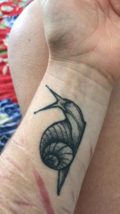 An arm with a snail tattoo.