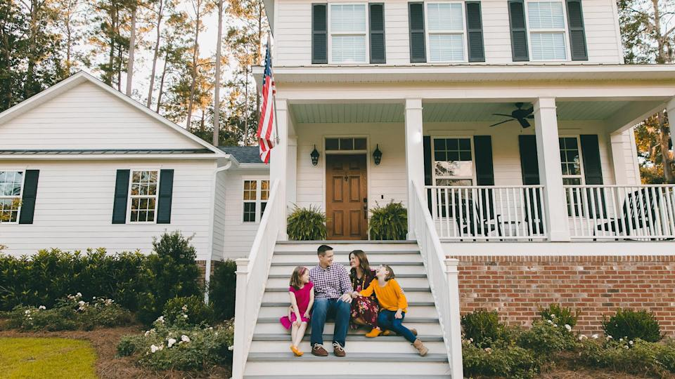 Family sitting outside on the steps of a new construction white siding farmhouse in the suburbs.
