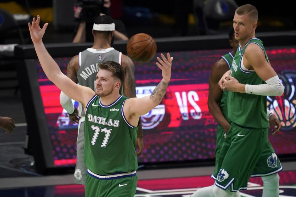 Luka Doncic raises his arms in celebration after making a shot with Marcus Morris walking away and Kristaps Porzingis looking over.