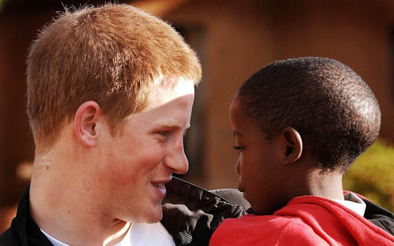 Prince Harry picks up and holds old friend Mutsu Potsane aged 6, in the grounds of the Mants'ase childrens home, while on a return visit to Lesotho in Southern Africa, Monday 24th April 2006. The Prince was in the country to launch his new charity called 'Sentebale', which means forget me not in memory of his mother Diana Princess of Wales - Credit: ITV