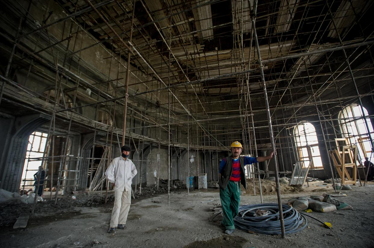 Men stand in a large chamber as Afghan workers rebuild the iconic Darulaman Palace, after decades in which its ruins were a reminder of constant conflict, on May 21, 2019, in Kabul, Afghanistan. (Scott Peterson/Getty Images)