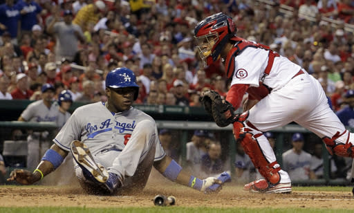 Los Angeles Dodgers' Yasiel Puig, left, scores past St. Louis Cardinals catcher Tony Cruz on a two-run single by Skip Schumaker during the second inning of a baseball game Wednesday, Aug. 7, 2013, in St. Louis. (AP Photo/Jeff Roberson)