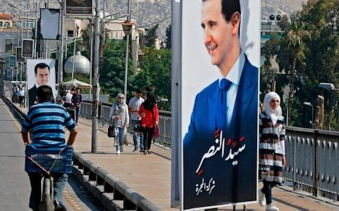 People walk near a portrait of Syrian President Bashar al-Assad hanging in a street in the Syrian capital Damascus  - Credit: AFP