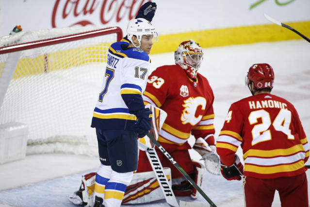 St. Louis Blues' Jaden Schwartz, left, celebrates his team's second goal as Calgary Flames goalie David Rittich looks away during the second period of an NHL hockey game in Calgary, Saturday, Nov. 9, 2019. (Jeff McIntosh/The Canadian Press via AP)