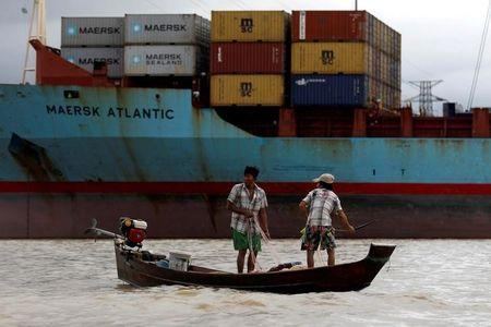 FILE PHOTO: Two fishermen stand on a boat in front of Myanmar industrial port terminal at the banks of the Hlaing river in Yangon, June 9, 2016. REUTERS/Soe Zeya Tun/File Photo