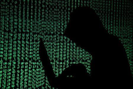 FILE PHOTO: Hooded man holds laptop computer as cyber code is projected on him in this illustration picture