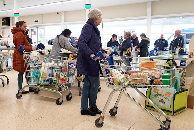 An elderly lady queues to pay for her shopping at a supermarket in Ashford, Kent, as UK, shoppers are emptying shelves as fears grow over the spread of the coronavirus.