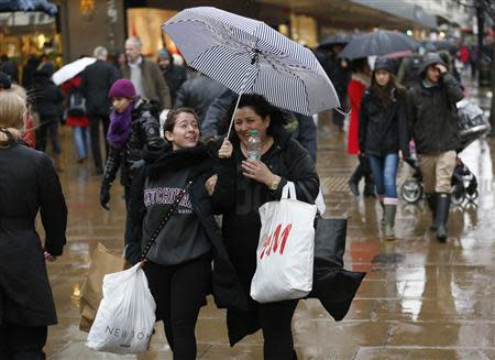 Shoppers walk in wet and windy weather on Oxford Street in central London December 23, 2013. REUTERS/Olivia Harris