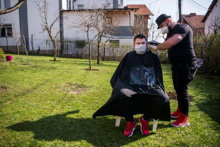 Kosovo barber Driton Kameri,(R), makes house calls to keep customers' hair in check (AFP Photo/Armend NIMANI)