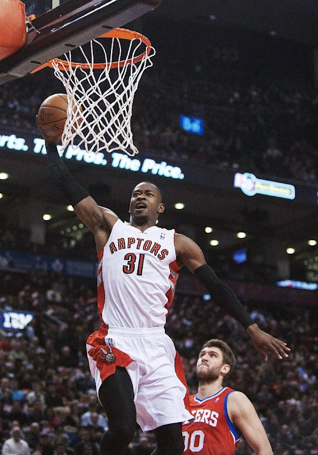 Toronto Raptors' Terrence Ross, left, slams the ball as Philadelphia 76ers' Spencer Hawes stands near during the first half of an NBA basketball game in Toronto on Friday, Dec. 13, 2013. (AP Photo/The Canadian Press, Aaron Vincent Elkaim)