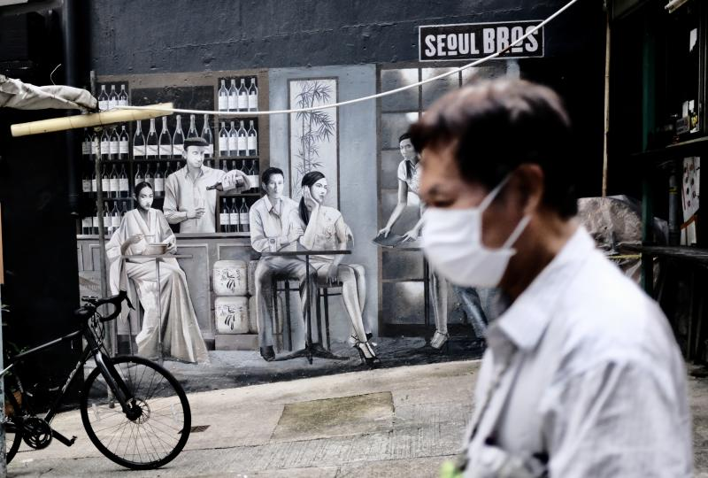 HONG KONG, CHINA - 2020/09/10: A pedestrian wearing a mask walks past a closed outdoor cafe in Hong Kong. A spokesman for the Food and Health Bureau said starting 11 Sept, the number of persons allowed in group gatherings in public places such as catering business premises will be increased from two to four. (Photo by May James/SOPA Images/LightRocket via Getty Images)
