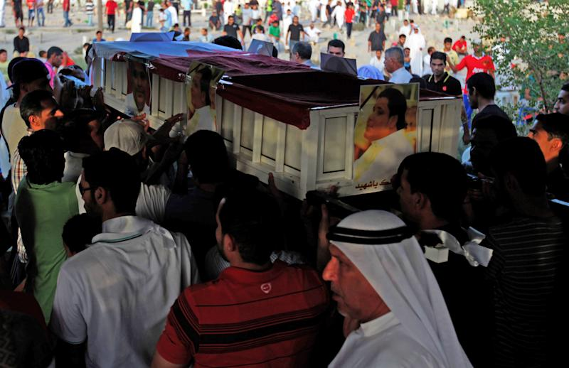 Bahraini mourners carry the flag-draped casket of Hussein Mansour Abdullah, 33, who authorities said died while being transported in a police jeep that flipped over on a highway, during his funeral in the western Shiite village of Malkiya, Bahrain, on Tuesday, July 30, 2013. Two police officers were injured in the crash, which became a politically sensitive matter because opposition activists said they hold authorities responsible for his well-being in custody. (AP Photo/Hasan Jamali)
