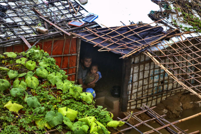 A Rohingya refugee man sits with his child inside his inundated shelter following heavy rains at the Rohingya refugee camp in Kutupalong, Bangladesh, Wednesday, July 28, 2021. Days of heavy rains have brought thousands of shelters in various Rohingya refugee camps in Southern Bangladesh under water, rendering thousands of refugees homeless. (AP Photo/ Shafiqur Rahman)