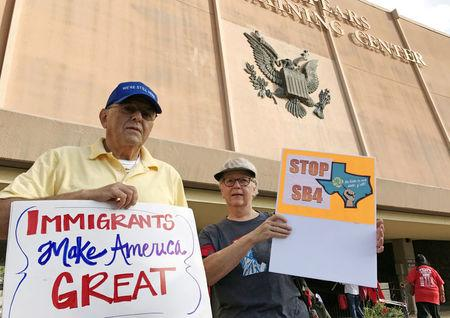 """FILE PHOTO:    Protesters against the Texas state law to punish """"sanctuary cities"""" stands outside the U.S. Federal court in San Antonio, Texas, U.S., June 26, 2017.  REUTERS/Jon Herskovitz/File Photo"""
